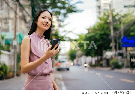 Cheerful Asian businesswoman using phone and waiting for taxi 69895600