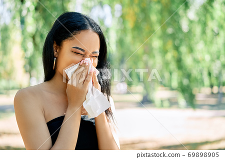 African american woman blows her nose into a tissue 69898905