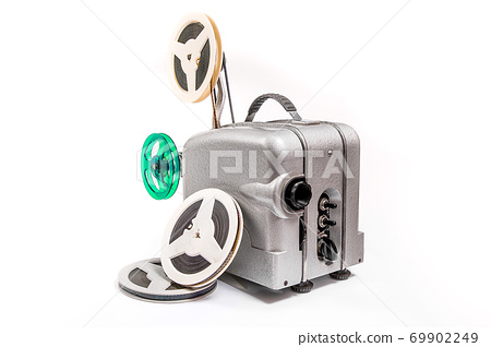 Vintage motion picture film projector and reel of motion picture film isolated on a white background. 69902249