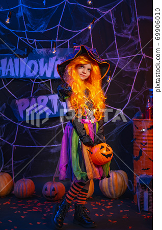 Little beautiful girl in a witch costume celebrates Happy Halloween party in interior with pumpkins 69906010
