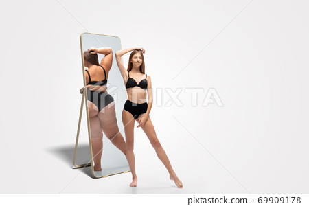 Young slim woman looking at fat girl in mirror's reflection on white background 69909178