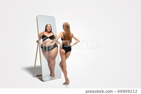 Young slim woman looking at fat girl in mirror's reflection on white background 69909212