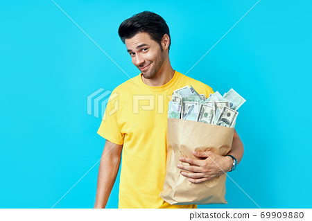 Funny man hold paper bag full of stacks of money isolated on blue background 69909880