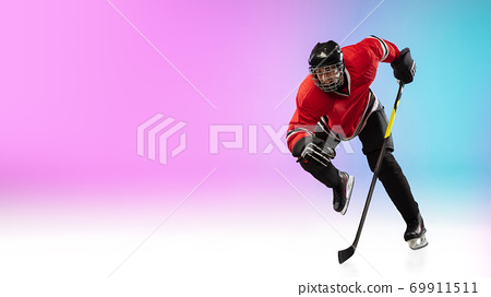 Male hockey player with the stick on ice court and neon colored gradient background. Sportsman wearing equipment, helmet practicing. 69911511