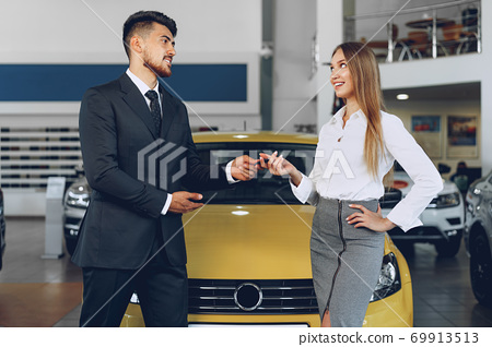 Young attractive woman buying a new car in car salon 69913513