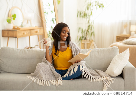 Pretty African American woman holding mug of coffee and reading book while sitting under warm plaid on sofa at home 69914714