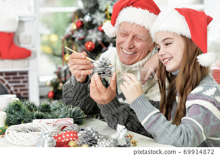 Grandfather with granddaughter in Santa hats preparing for Christmas at home 69914872