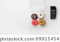 Sweets and bakery order takeaway. Donuts with glaze and crumb in transparent container for delivery and modern contactless terminal 69915454