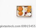 Modern fast lunch for two. Hamburger and cheeseburger, ketchup and sauce in containers, french fries in paper bags and cup of coffee in box 69915455
