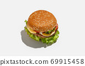 Fast food, takeaway for snack or client order for home during coronavirus. Tasty cheeseburger with lettuce, tomatoes and sesame seeds 69915458