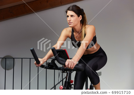 woman spinning at home exercising for their legs and cardio training 69915710