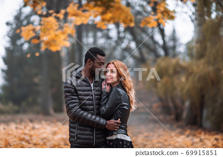 Happy Interracial couple posing in blurry autumn park background 69915851