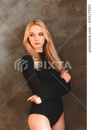 Woman with wavy hair. Sensual gorgeous young lady in black bodysuit posing in the studio 69917005
