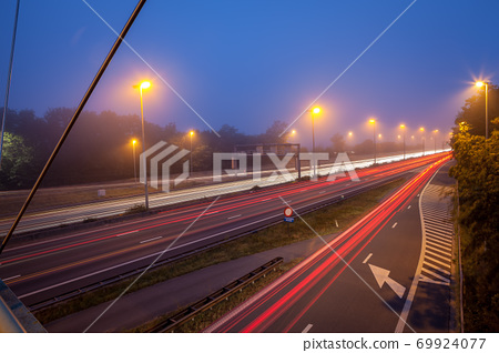 Bridge over freeway in the early morning with fog 69924077