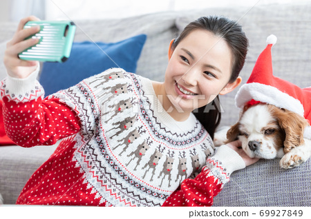 크리스마스 스웨터를 입고 애완 동물 사진을 찍는 여성 69927849