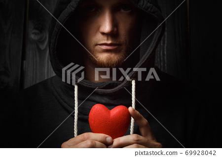 red heart in hands on a dark background 69928042