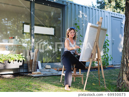 Portrait of mature woman with pallete painting outdoors in garden. 69930073