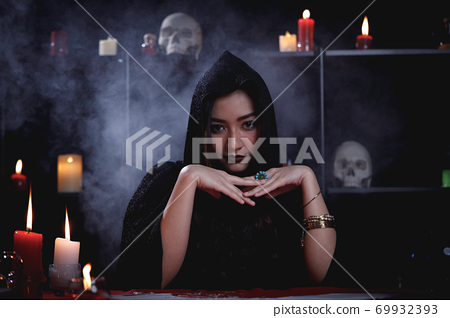Portrait of Asian mystery fortune teller in black robe with smoke background. 69932393