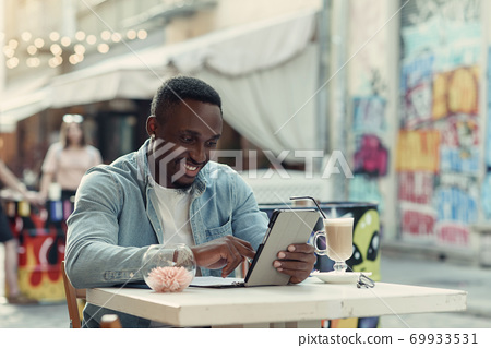 Young happy african american man uses tablet pc sitting on street cafe with graffiti on backdrop. 69933531