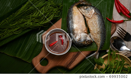 Fried mackerels with shrimp paste sauce and vegetable set served on Thai traditional plate 69935002