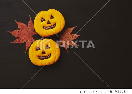 Funny Halloween jack o lantern pumpkin cookies and dry autumn leaves. 69937203