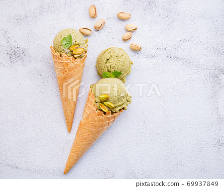 Pistachio ice cream in cones  with pistachio nuts setup on white stone background . Summer and Sweet menu concept. 69937849