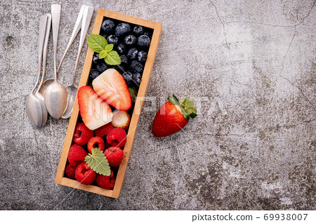 Various fresh berries blueberry, raspberry and strawberry in woo 69938007