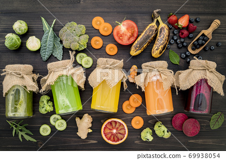 Colourful healthy smoothies and juices in bottles with fresh tro 69938054
