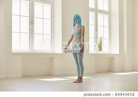 Girl with blue hair standing with fitness carpet ready for sports workout in studio 69943658