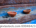 Oil Lamp Pooja Diya Lamp on blue house wall in Jodhpur, Rajasthan, India 69946423