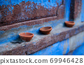 Oil Lamp Pooja Diya Lamp on blue house wall in Jodhpur, Rajasthan, India 69946428