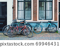 Bicecles which are a very popular transport in Netherlands parked in street near old houses 69946431