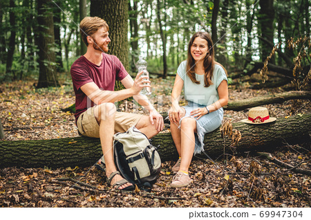Couple relaxing sitting on a log and drinking water. The family is enjoying a romantic weekend in nature. A pleasant walk or a romantic date in the background of nature. Picnic hike in the forest 69947304