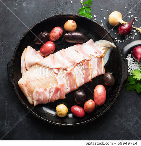 White cod fish wrapped in raw smoked bacon slices in a baking dish with new potatoes, spices and herbs. Top view. On a dark background 69949714