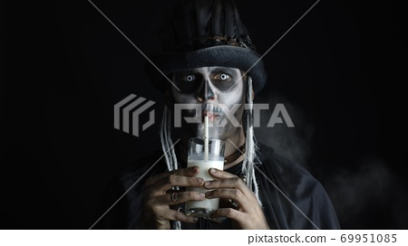Creepy man with skeleton makeup in top-hat. Guy looking at camera, drinks milk from a glass 69951085