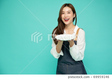 Young Asian woman in apron standing and holding empty white dish isolated on green background 69959146