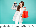 Midnight sale concept Portrait of a happy young woman holding shopping bags and black alarm clock. 69959150