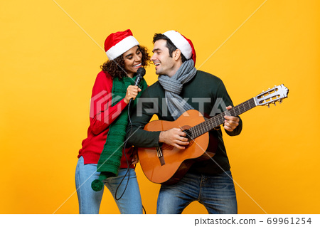 Happy interracial couple singing a song celebrating Christmas 69961254