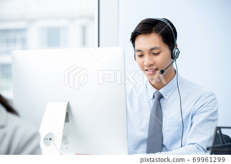 smiling male Asian telemarketing staff working in call center  69961299