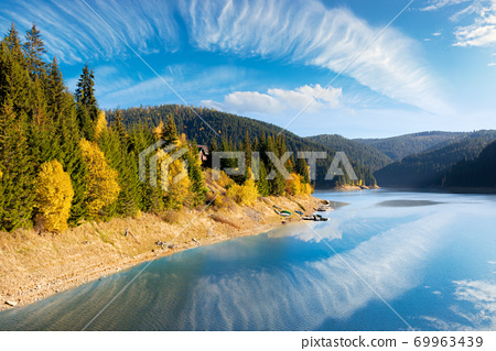 mountain lake in autumn season. beautiful countryside scenery on a sunny morning. bright blue sky with fluffy clouds reflecting on the water surface 69963439