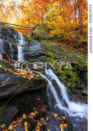 waterfall in the autumn forest. trees in colorful foliage. water runs among the rocks. fallen leaves on the shore. beautiful fall scenery on a sunny day 69963454