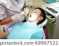 Dentist examining boy mouth 69967522