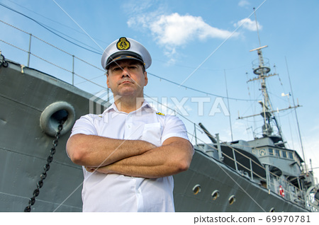 Captain standing in dock before warship and  looking ahead.  69970781