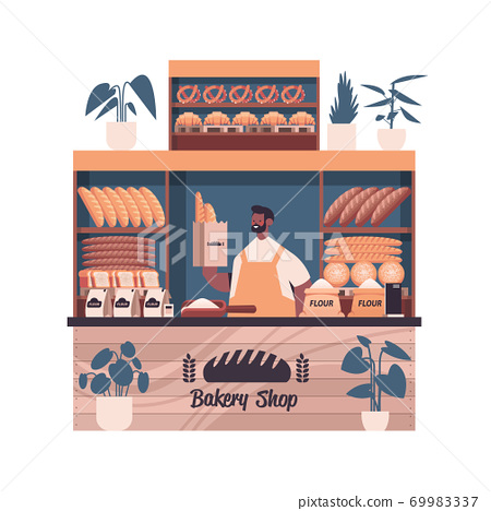 male baker holding bag with baguettes man in uniform selling fresh bakery products in baking shop 69983337