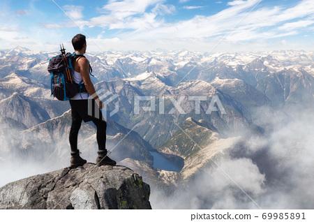 Adventurous Man Hiker on top of a Steep Rocky Cliff 69985891