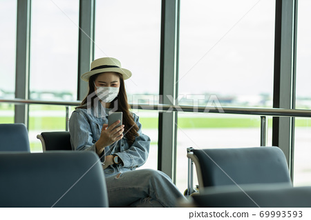 Asian young woman traveller wearing face maks using mobile phone at airport Due Covid-19 flu virus pandemic and protection 69993593