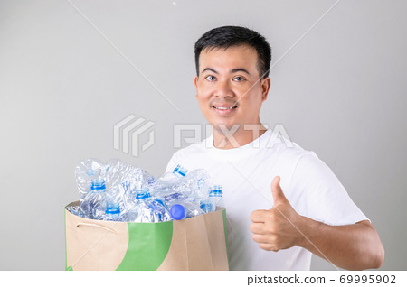 Portrait Asian man holding many empty clear old water bottle. Studio shot on grey background 69995902