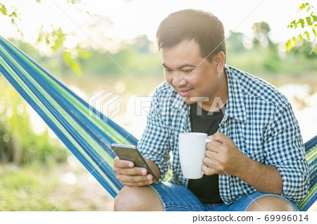 Man sitting on hammock and holding coffee cup and smartphone. Outdoor shooting with morning sunlight effect 69996014