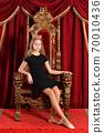 Portrait of happy girl princess posing on throne 70010436