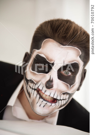 Man with make-up Halloween. Drawing a vampire, skeleton 70010792